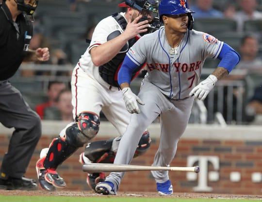 New York Mets Marcus Stroman bunts his way onto base as Atlanta Braves catcher Brian McCann reacts in the fifth inning of a baseball game Thursday, Aug. 15, 2019, in Atlanta. (AP Photo/Tami Chappell)