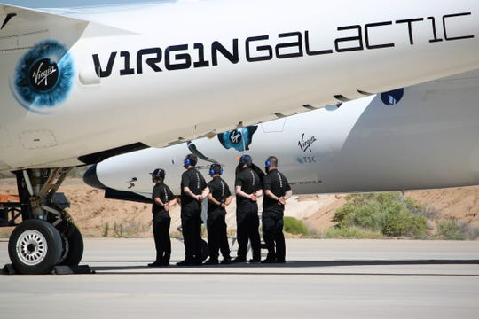 Virgin Galactic ground crew waits for the pilots of the WhiteKnightTwo carrier aircraft to disembark after landing at Spaceport America on Thursday, August 15, 2019.