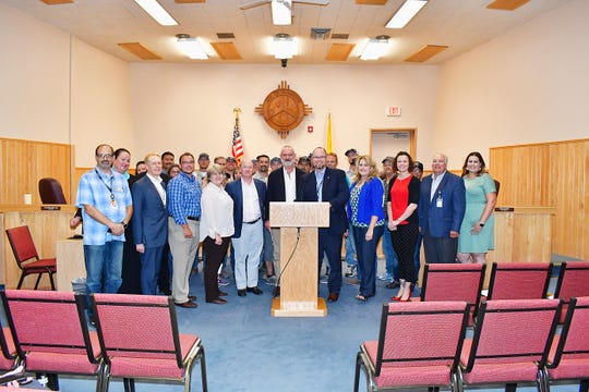 Farmington and Enchant Energy officials as well as audience members stand for a photo Aug. 15 at the end of a special council meeting.