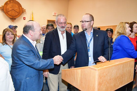 Enchant Energy CEO Jason Selch shakes hands with Farmington Mayor Nate Duckett, Thursday, Aug. 15, 2019, during a special council meeting.