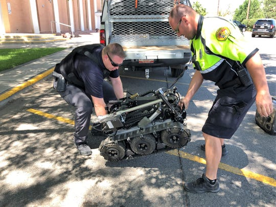 Members of the Farmington Police Department unload a robot in the St. Mary's Catholic Church parking lot on 2100 E. 20th St. on Aug. 15 while responding to a cal regarding a barricaded man.