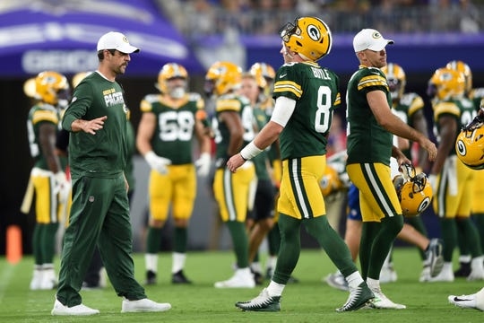 Green Bay Packers quarterback Aaron Rodgers, left, greets quarterback Tim Boyle after a series against the Baltimore Ravens during the first half of a NFL football preseason game, Thursday, Aug. 15, 2019, in Baltimore. (AP Photo/Gail Burton)