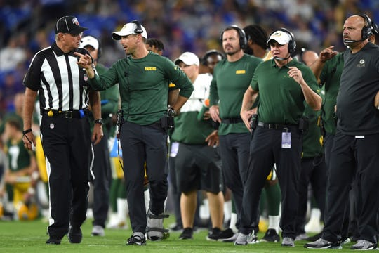 Green Bay Packers head coach Matt LaFleur, second from left, talks to an official during the second half of an NFL football preseason game against the Baltimore Ravens, Thursday, Aug. 15, 2019, in Baltimore. (AP Photo/Gail Burton)