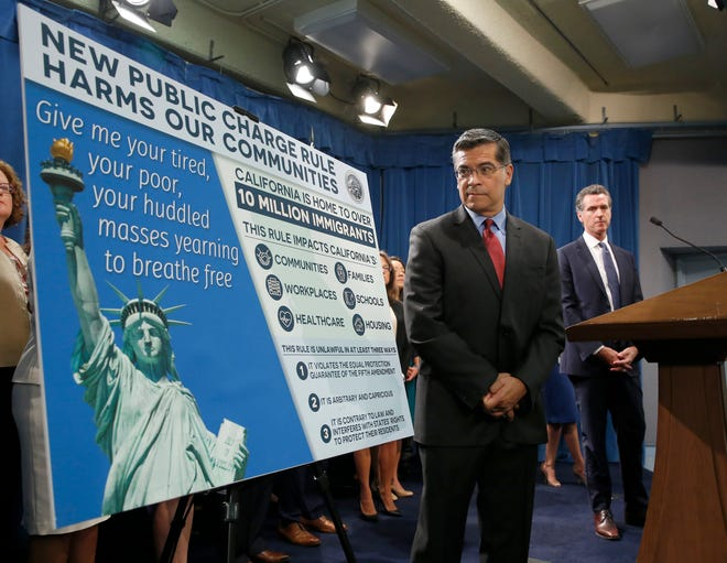 California Attorney General Xavier Becerra, left, glances at a display outlining the supposed effects on immigrants in the state under the Trump administration's new rules blocking green cards for many of those who receive government assistance.
