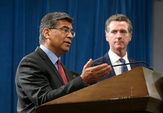 California Attorney General Xavier Becerra, left, flanked by Gov. Gavin Newsom, discusses the lawsuit the state has filed against the Trump administration's new rules blocking green cards for many immigrants who receive government assistance, during a news conference in Sacramento, Calif., Friday, Aug. 16, 2019. California, three other states and the District of Columbia filed the suit Friday against some of the administration's most aggressive moves to restrict legal immigration that are supposed to take effect in October. (AP Photo/Rich Pedroncelli)