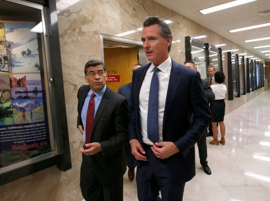 California Gov. Gavin Newsom, right, and Attorney General Xavier Becerra, leave a news conference where they announced the state has filed a lawsuit against the Trump administration's new rules blocking green cards for many immigrants.