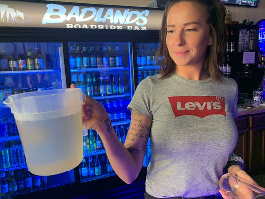Amy Rutledge, a bartender at Badlands Roadside Bar on Palafox, holds a pitcher of dirty water that was coming out of the faucets for about three hours on Friday. The bar had clean water restored at around 3:30 p.m.