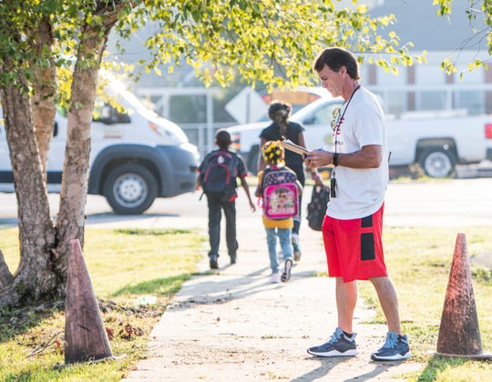 Physical education teacher Lou Henry supervises approved tunnel walker students as they make their way to Brentwood Elementary School on North Palafox Street on Aug. 16. Approved students make their way through a tunnel under the heavy traffic of Palafox Street.