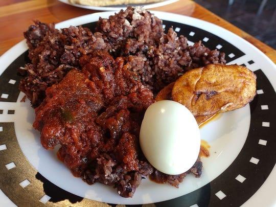 Waakye con estofado de cabra, plátanos fritos y huevo duro en Jollof King en Tempe.