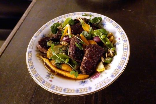 Medallones de filete de hierro fundido en queso cheddar envejecido con frijoles tepary, champiñones y vegetales de temporada en Cotton & Copper en Tempe.