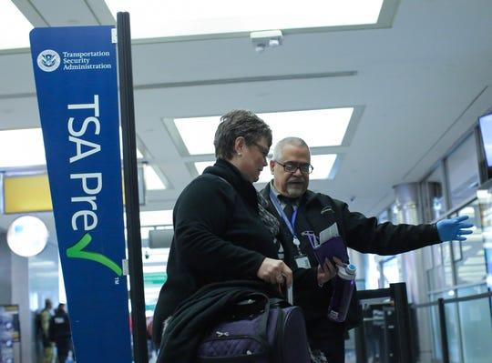 Un empleado del aeropuerto ayuda a una señora en el aeropuerto.