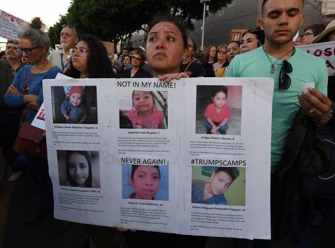 Una mujer sostiene una pancarta, que incluye fotos de los niños que han muerto bajo custodia de autoridades de EEUU.