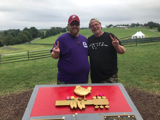Phil Tarricone, left, and his father, John, at the Woodstock monument on the original Woodstock festival site at Bethel Woods Center for the Arts in Sullivan County.
