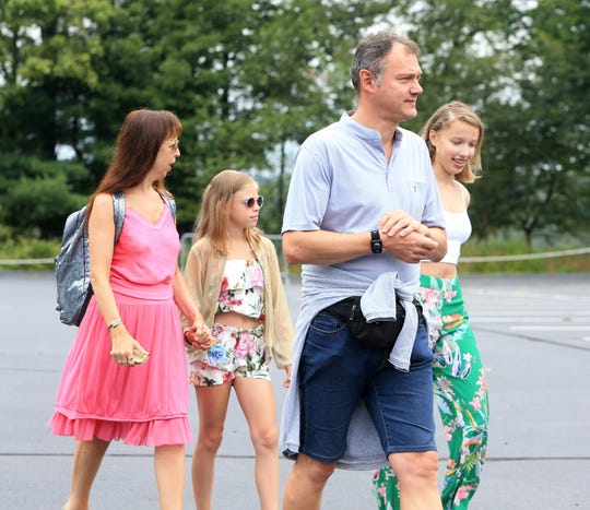 From left, Caroline Loods with her family, Anais, Bart and Kyara Smeets from Belgium make their way to the to the main gate of Bethel Woods Center for the Arts to celebrate the 50th anniversary of Woodstock on August 16, 2019. The family planned their trip to the USA to coincide with the Woodstock celebration.