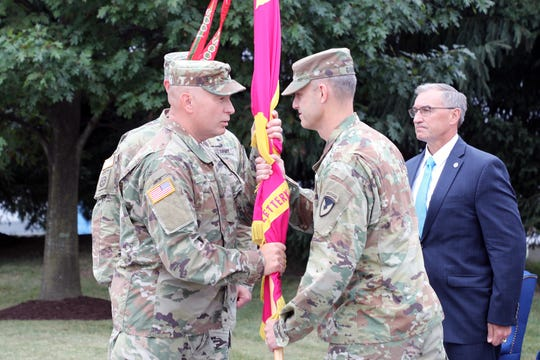 Sergeant Major Rich Huff, left, receives the Letterkenny Army Depot colors from Col. Gregory Gibbons as he takes on his new role as commander. Bill Marriott, right, executive director of the U.S. Army Aviation and Missile Command, presided over the ceremony.