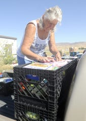 Troyann Cada loads food into the back of a delivery truck.