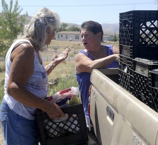 Troyann Cada (left) and Billie Jo Miller unload a crate of food.