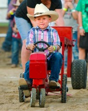 Gregory Ward, 7, pedals hard in the kids' tractor pull.