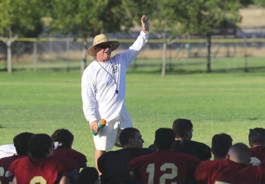 West Valley head varsity football coach Greg Grandell talks to his players at the end of their practice on Tuesday, Aug. 13, 2019.