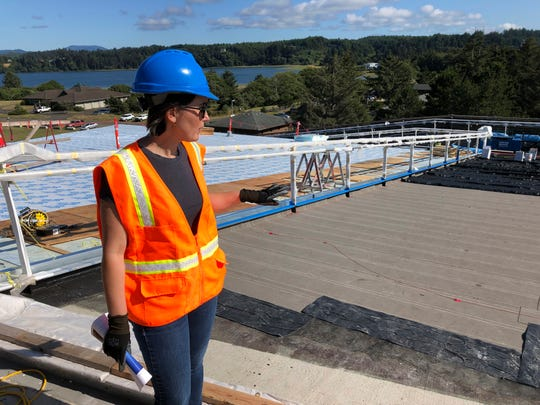 Crystal Sanderson with Portland-based Yost Grube Hall Architecture, shows reporters an emergency access ramp that is being built alongside Oregon State University's Marine Studies Building, which is under construction in Newport, Ore. The roof will serve as a vertical evacuation zone for almost 1,000 fleeing a tsunami that an offshore quake would generate, and the ramp will be open around the clock.