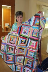Julie Luce holds one of 18 quilts she made and donated to the Ronald McDonald House Charities of Central Texas, 1315 Barbara Jordan Blvd. in Austin, on Thursday, Aug. 8.