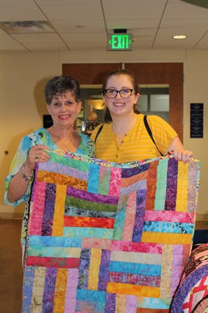 Julie Luce and her granddaughter Berkeley hold one of 18 quilts presented to the Ronald McDonald House Charities of Central Texas, 1315 Barbara Jordan Blvd. in Austin, on Thursday, Aug. 8.