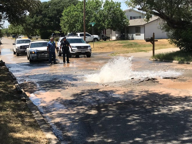 San Angelo police officers watch water burst from the road in the 100 block of Madison Street on Friday, Aug. 16.