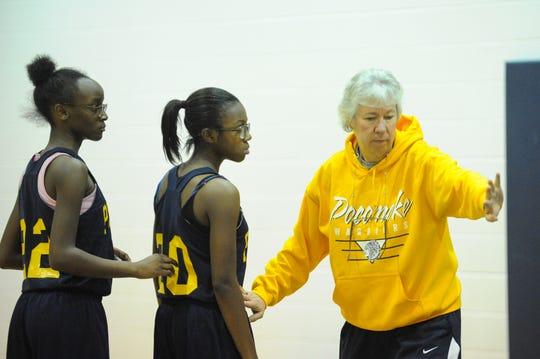 Pocomoke High School girls' basketball head coach Gail Gladding assists her team run through drills during practice.