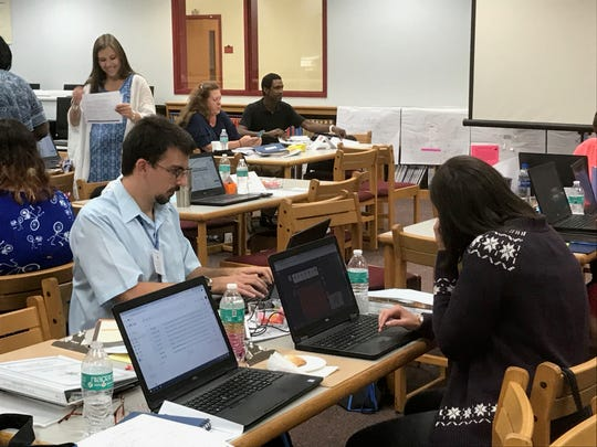 Brother and sister Corbin and Rebecca Davis work on their laptops during an orientation for new teachers in Accomack County Public Schools in Oak Hall, Virginia on Thursday, Aug. 15, 2019.