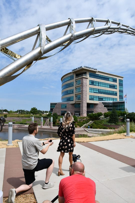 Tyler Meints readies to propose to his now-fiance Stacia Rawhouser. The couple believe they were the first to get engaged under the Arc of Dreams sculpture.