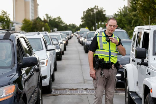 A Springfield police officer directs a long line of traffic during move-in day Aug. 16 at Missouri State University. There are 10 officers assigned to a police substation on campus.