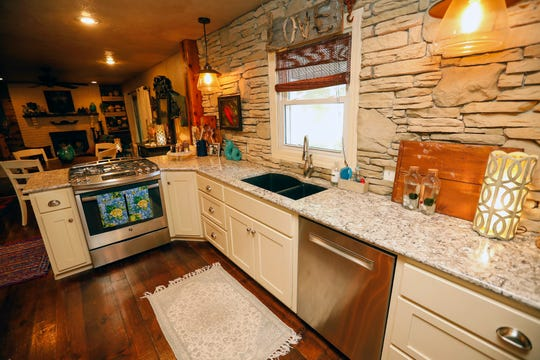 Jenn's kitchen features a stone wall, ample counter space and a clear view of both dining and living areas.