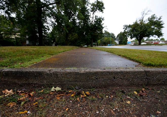 A sidewalk running along North Benton Avenue, across from Cox North Hospital, is cut off by an alleyway with no curb ramp.