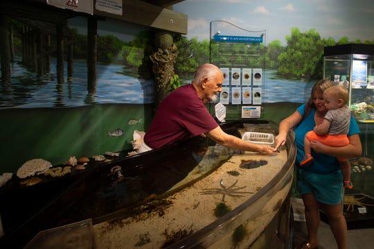Smithsonian Marine Ecosystem Exhibit volunteer John Hallam, of Vero Beach, assists Caroline Castle, of Vero Beach, and her son, John Castle, 18 months, on Friday, Aug. 16, 2019 at the St. Lucie County Aquarium in Fort Pierce.