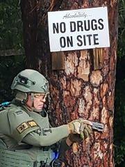SWAT member Dr. James Betancourt raids the home in the 6300 block of 85th Street. This sign was posted to this tree by residents of the area.