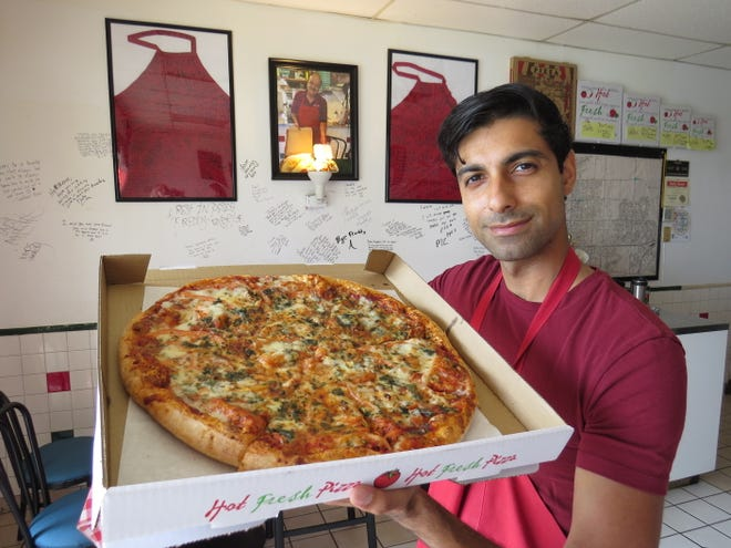 "Masud Majeed, son of late Oxnard pizzeria owner Abdul Farid ""Freddy"" Majeed, poses in the dining room of the Patterson Road restaurant. Formerly known as Ameci Pizza & Pasta, the family-owned business has been renamed Freddy's Pizza."