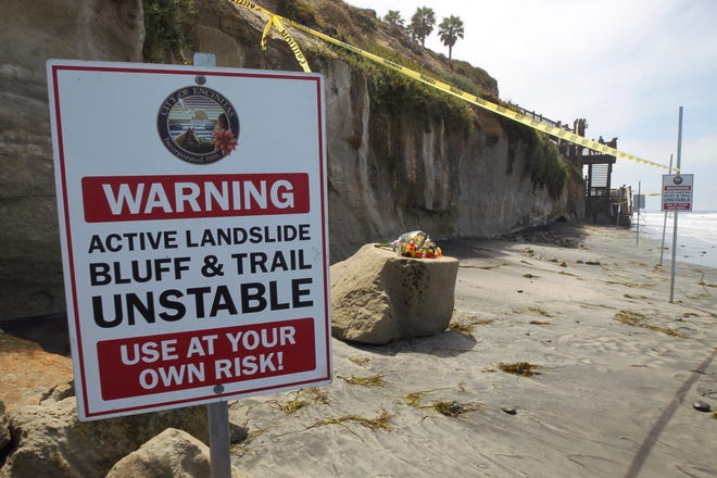One of several warning signs is posted next to the sand rock debris left from a sea cliff collapse that killed three people near the Grandview Beach access stairway in the beach community of Leucadia, Saturday, Aug. 3, 2019, in Encinitas, Calif. A bouquet of flowers has been placed one of the chunks of sand stone. (Hayne Palmour IV/The San Diego Union-Tribune via AP)