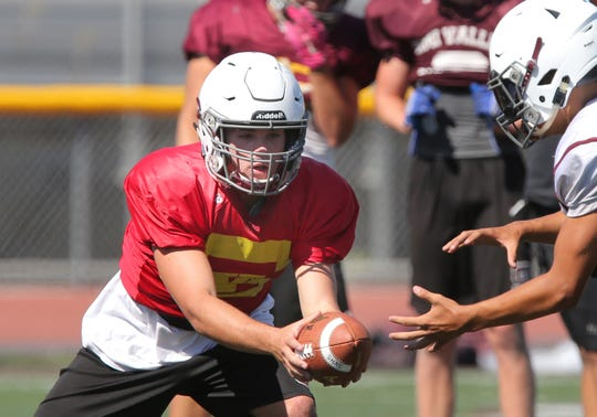 Simi Valley High quarterback Jack Applegate hands the ball off to one of his running backs during a recent practice.