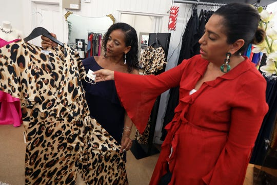 Sales associate Ada Basabe Cruz, left, and owner Manal Flournoy pair a dress with earrings at Runway on the Hudson Aug. 16, 2019 in Nyack. Flournoy, a mom of two and fashion lover, recently opened a second clothing boutique in Tuxedo.