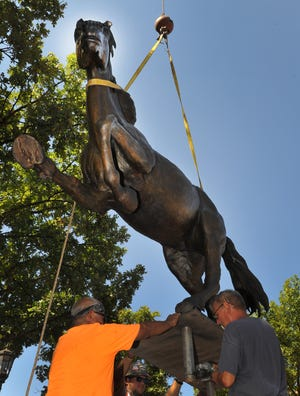 Midwestern State University construction crews work to install one-of-four Mustang statues designed and constructed by Vic Payne Studios. The statues will represent each class at MSU and will stand in front of the Centennial Hall building.
