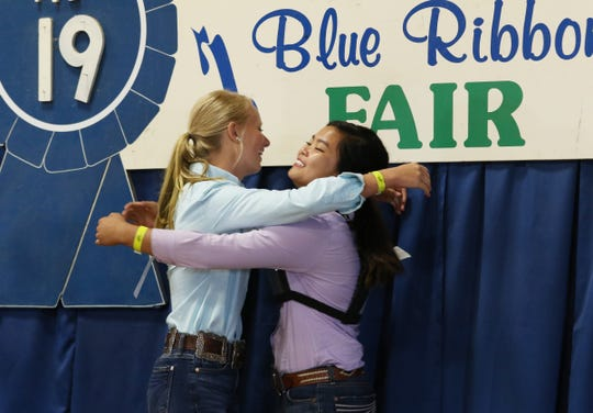 Kristina Scheurman, right, gets a hug from second-place finisher Kamryn Kreis after Scheurman won the Showman of Showmen at the Muskingum County Fair on Friday.