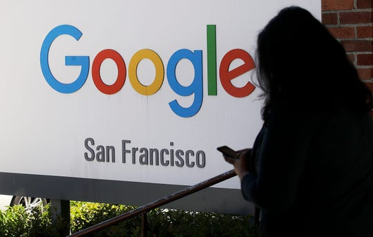 In this May 1, 2019, file photo, a person walks past a Google sign in San Francisco. Google employees are calling on the company to pledge it won't work with U.S. Customs and Border Protection or Immigration and Customs Enforcement, the latest in a year full of political and social pushback from the tech giant's workforce.