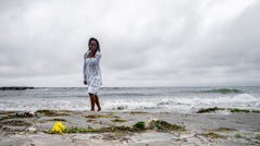 "Samantha Lewis, wipes away tears after reflecting on the ""Day of Remembrance,"" which honors Africans who were captured as slaves and died during the Middle Passage. The remembrance was at Virginia Beach on Saturday, Jun 8, 2019 in Hampton, Va."