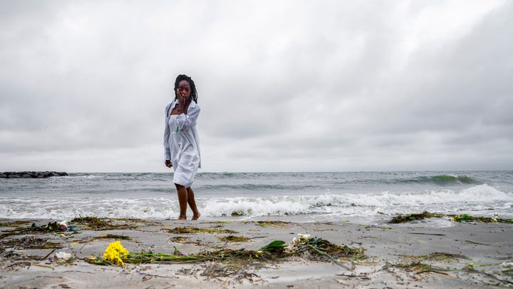 """Samantha Lewis, wipes away tears after reflecting on the """"Day of Remembrance,"""" which honors Africans who were captured as slaves and died during the Middle Passage. The remembrance was at Virginia Beach on Saturday, Jun 8, 2019 in Hampton, Va."""