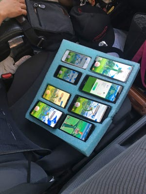In this photo provided by the Washington State Patrol, a piece of foam, cut to hold eight mobile phones in place – all of them playing the game Pokemon GO – is shown on the passenger seat of a vehicle driven by a person who was found pulled over on the shoulder of a highway near Seattle by a state trooper who thought the driver needed assistance.
