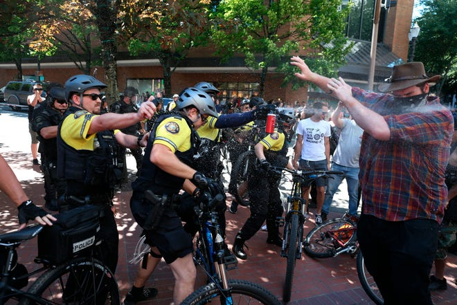 In this June 29, 2019, file photo, after a confrontation between authorities and protesters, police use pepper spray as multiple groups, including Rose City Antifa, the Proud Boys and others protest in downtown Portland, Ore. Portland police are mobilizing in hopes of avoiding clashes between out-of-state hate groups planning a rally Saturday, Aug. 17, 2019, and homegrown anti-fascists who say they'll come out to oppose them.