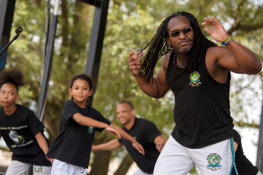 Professor Show Grande leads dancers in Capoeira during Battle Creek's International SummerFest on Saturday, Aug. 17, 2019 at Kellogg Community College in Battle Creek, Mich. Capoeria is an Afro Brazilian dance the incorporates martial arts.