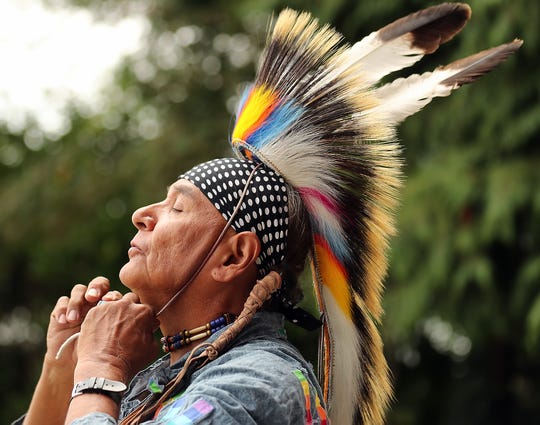 Medicine Bear Lone Warrior, a member of the Sioux tribe who lives in La Connor, ties his headdress underneath his chin as he gets ready for the start of the Chief Seattle Days Powwow in Suquamish, on Saturday, August 17, 2019.
