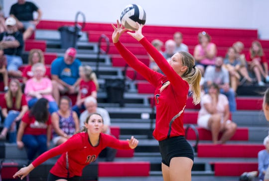 Crestview's Alyssa Derr sets the ball as Elly Motter looks on.