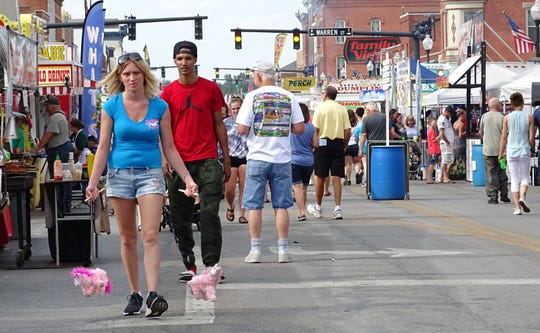 A woman carries two marionette toys along the midway Friday at the Bucyrus Bratwurst Festival.